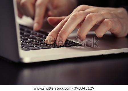 Female hands using laptop on dark wooden table, close up