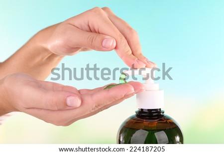 Female hands using liquid soap on light background - stock photo