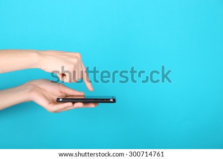 Female hands using mobile phone on blue background - stock photo