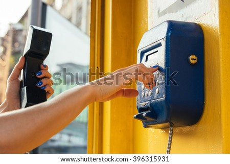 Female hands using the pay phone in the city - stock photo