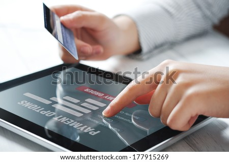 Female hands using touch screen device for online payment - stock photo