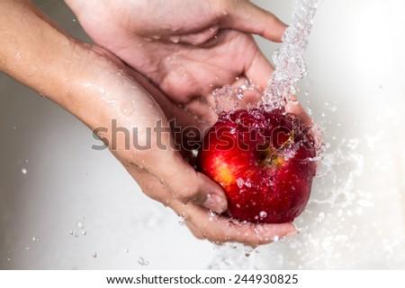 Female hands washing apple - stock photo