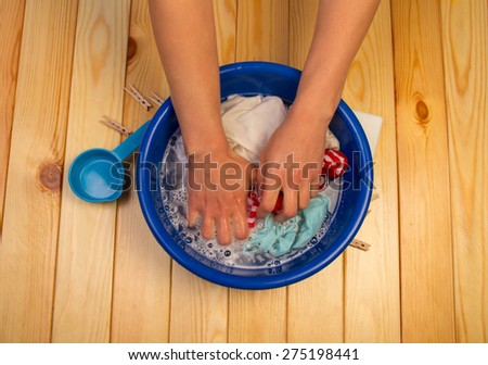 Female hands washing in bucket on wooden background - stock photo