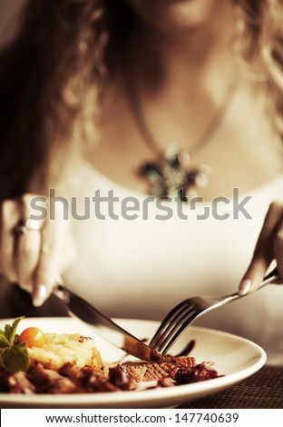 Female hands with a dinner at restaurant - stock photo