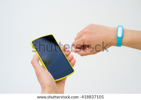 Female hands with a sports bracelet and smart phone close up on a white background, not isolate - stock photo