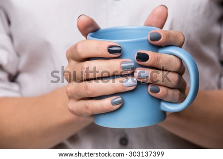 Female hands with blue cup - stock photo