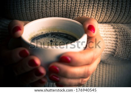 Female hands with coffee drink, knitted sweater - stock photo