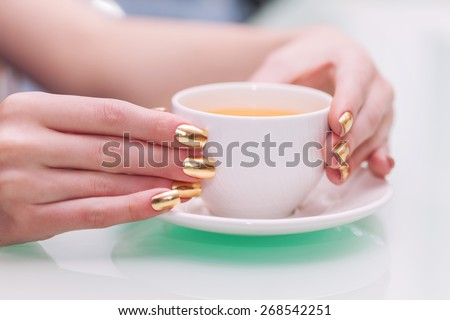 Female hands with elegant gold manicure hold a cup of tea - stock photo