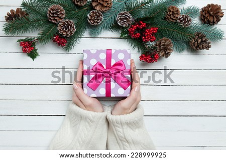 Female hands with gift box and pine branches. - stock photo