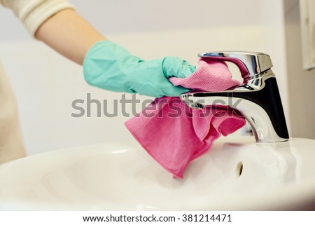 Female hands with green rubber protective gloves cleaning tap with pink cloth. Spring cleaning