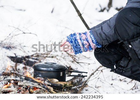 Female Hands with Handwarmers Getting Warm Near Fire Place - stock photo