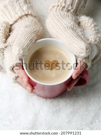 Female hands with hot drink, on light background - stock photo