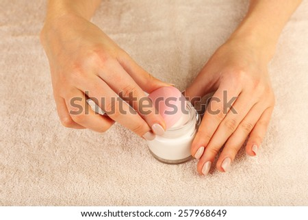 Female hands with jar of cream on fabric background