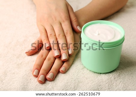Female hands with jar of cream on fabric background - stock photo