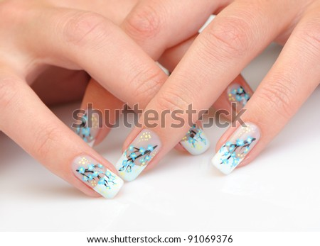 Female hands with manicure close up. Drawing of a branch with blue flowers. It is isolated on a white background. - stock photo