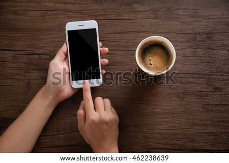 Female hands with mobile phone and cup of coffee on wooden background