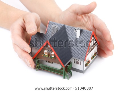 Female hands with model of house on a white background. Concept  of buying and insuring  real estate.