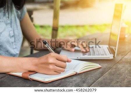 Female hands with pen writing notebook and using laptop on desk table at coffee shop. - stock photo
