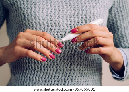 Female hands with pink manicure holding cosmetic product - stock photo