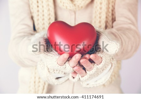 Female hands with red heart, close-up. Retro style