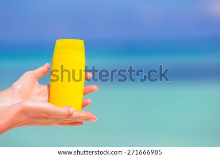 Female hands with suncream bottle background blue sea - stock photo