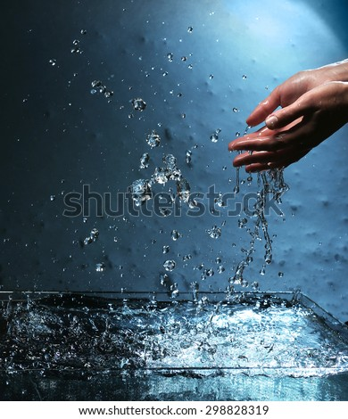 Female hands with water splashing on blue background - stock photo