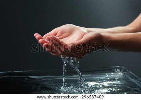 Female hands with water splashing on dark background - stock photo