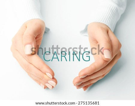 Female hands with word caring on light background - stock photo