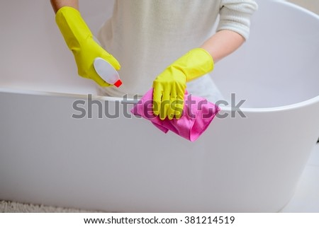 Female hands with yellow rubber protective gloves cleaning bath with pink cloth and spray detergent. Spring cleaning