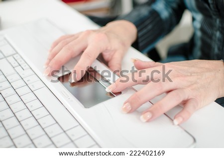 Female hands working on a white laptop computer keyboard