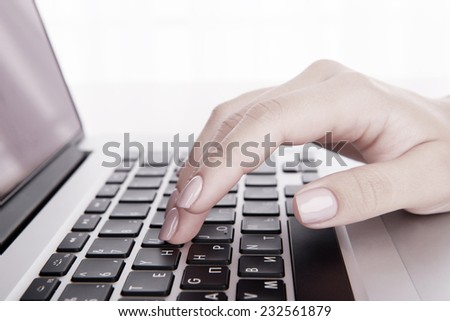 Female hands working on laptop on light background