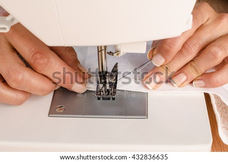 Female hands working with a sewing machine - stock photo