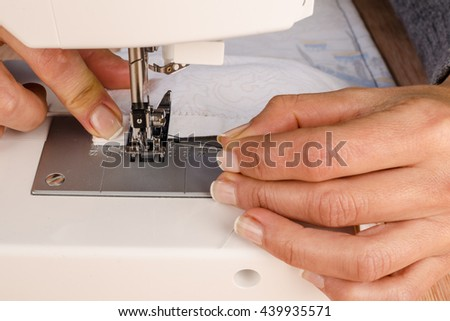 Female hands working with a sewing machine