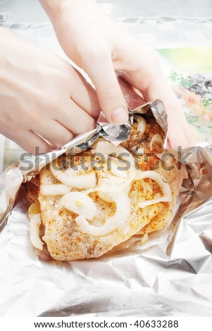 Female hands wrapping raw chicken meat marinated with pieces of fresh onion on aluminum food foil, selective focus