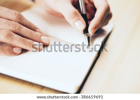Female hands writing in notebook with pen on wooden table