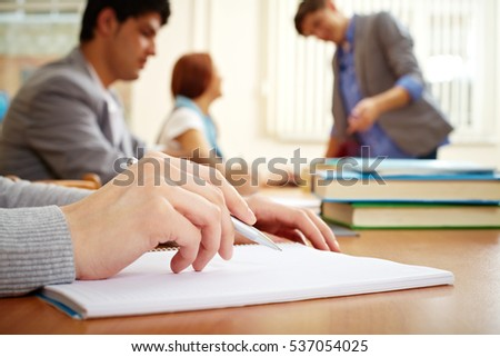 Female hands writing in workbook in college