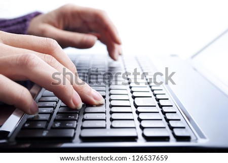 female hands writing on laptop, close-up shot - stock photo