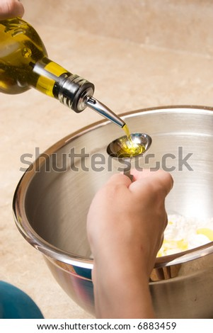 female hang adds just a little olive oil to the mixture - stock photo