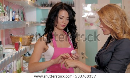 Female happy consultant offering customers cosmetics in beauty shop
