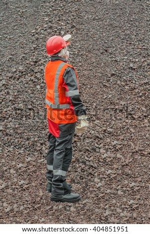 Female hard work. harmful production. mining industry.  warehouse. waste. ore. raw materials. Dust content of air. Harmful air. The woman in protective working clothes. labor protection - stock photo