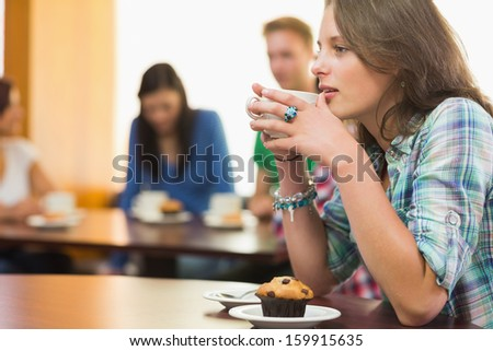 Female having coffee and muffin with students around table in background at  the coffee shop - stock photo