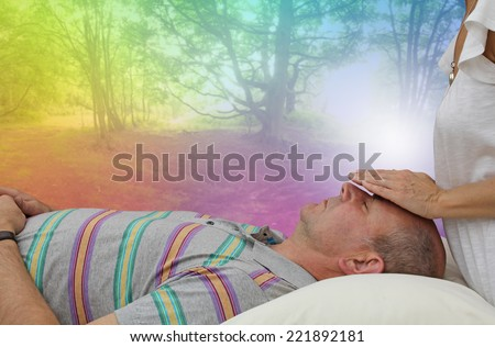 Female healer standing behind supine male client with hands hovering over his face  channeling healing with a fantasy rainbow colored woodland scene in the background - stock photo