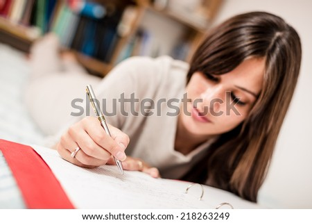 Female high school student making notes - stock photo