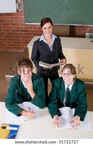 female high school teacher and her students in classroom - stock photo