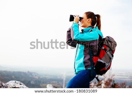 Female hiker admiring the view through binoculars - stock photo