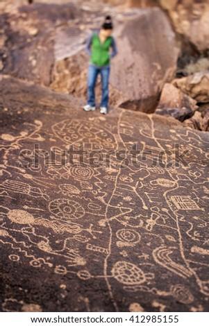 Female hiker contemplating ancient native American rock art. - stock photo