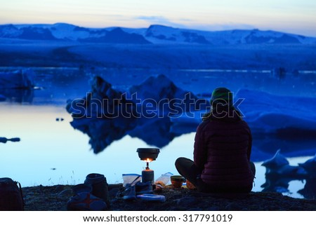 Female hiker cooking on her campsite at the Jokulsarlon lagoon on Iceland at dusk. - stock photo