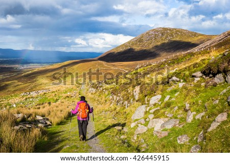 Female hiker hiking in the mountains in Ireland with rain and rainbow in the distance - stock photo