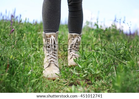 Female hiker legs with boots walking through meadow at sunny day