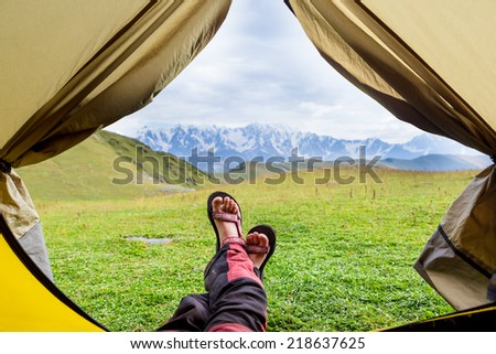 Female hiker llying in tent with a view of mountain  - stock photo